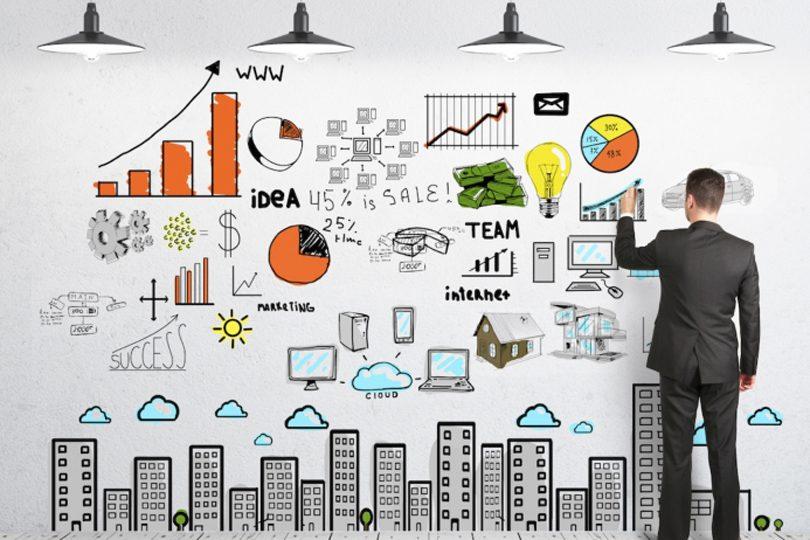 کارآفرینی یا کارمندی ــ مردی در برابر دیواری شامل نمودارها ایستاده است