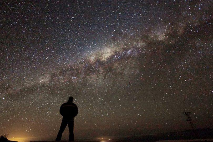 معنای زندگی ــ تصویر مردی در زمینهٔ آسمان شب با کهکشان راه شیری