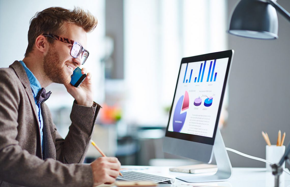 مردی در برابر کامپیوتر در حال تماس تلفنی است