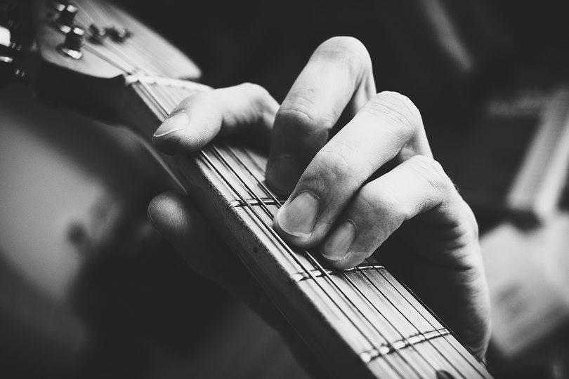 هنرجویی در حال تمرین کردن گیتار است